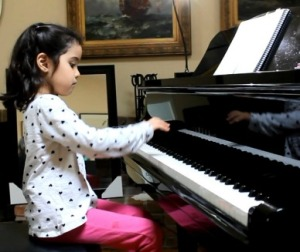 Four year old student plays a piece